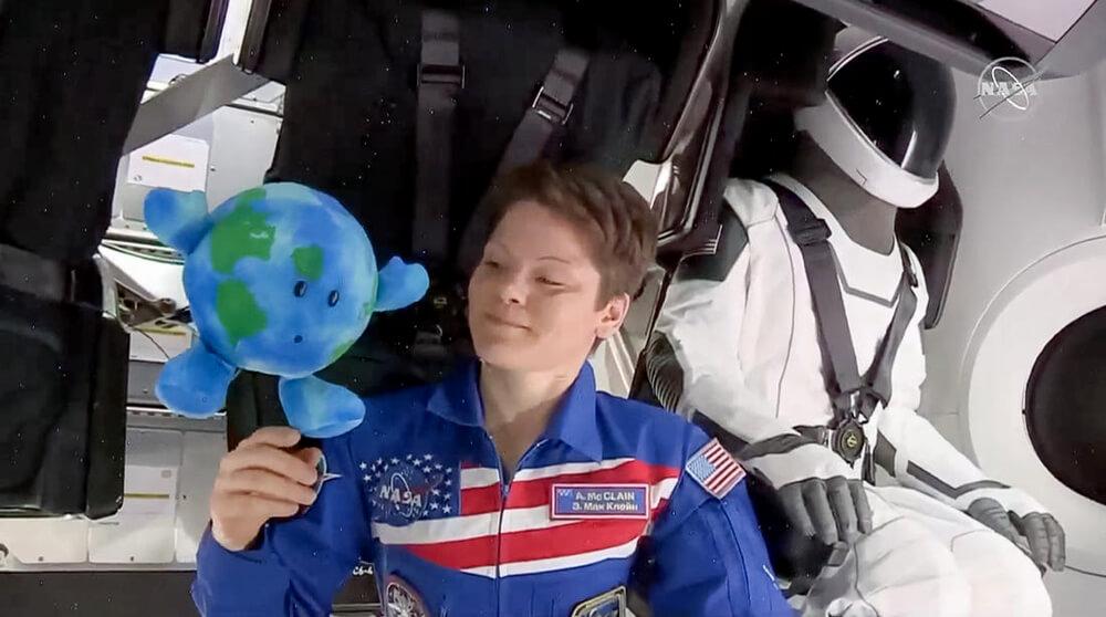 Astronaut Anne McClain speelt met aarde-knuffel Buddy in SpaceX's Crew Dragon